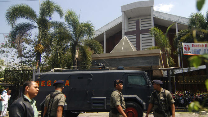 Indonesian police officer stands guard near an armored vehicle outside a church after an explosion in Solo, Central Java, Indonesia, Sunday, Sept. 25, 2011. A suicide bomber attacked the church packed with hundreds of worshippers Sunday, killing himself and wounding at least 20 other people, police and hospital officials said. (AP Photo)