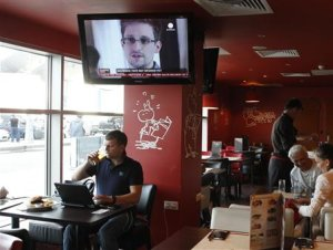 A television screen shows former U.S. spy agency contractor Snowden during a news bulletin at a cafe at Moscow's Sheremetyevo airport