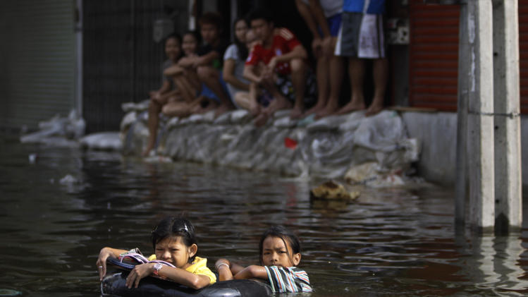 Thai girls swim in floodwaters with the help of inflated tubes in a flooded neighborhood in Bangkok, Thailand, Saturday, Nov. 5, 2011. Floodwaters lapped Bangkok's largest outdoor market Saturday as officials warned that there were no major barriers between the water and the heart of the Thai capital, less than 6 miles (10 kilometers) away. (AP Photo/Altaf Qadri)