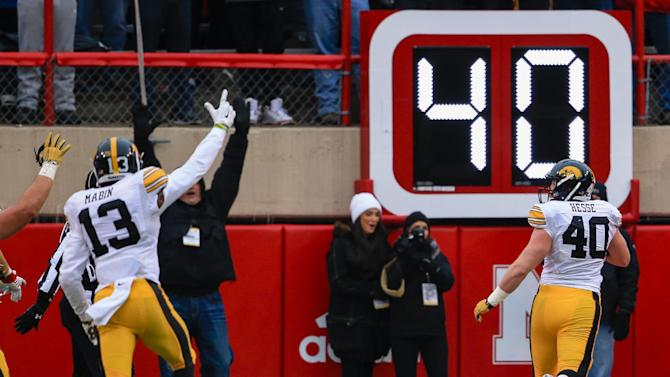 Iowa linebacker Parker Hesse (40) scores a touchdown after intercepting a throw by Nebraska quarterback Tommy Armstrong Jr. (4) during the first half of an NCAA college football game in Lincoln, Neb., Friday, Nov. 27, 2015. (AP Photo/Nati Harnik)