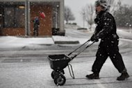 Ann Dass of Bent Mountain Va. spreads salt on a business parking lot in Christiansburg Va. Thursday Jan. 17 2013. Dass and her brother David Taylor, left background, are part of Acme Snow and Ice Removal and were trying to get the upper hand on the oncoming winter storm. &quot;I&#39;m sure we&#39;ll be back&quot; said Dass about the quickly accumulating snowfall and the challenge of removing it. (AP PHOTO/The Roanoke Times, Matt Gentry) (AP Photo/The Roanoke Times, ) LOCAL TV OUT; SALEM TIMES REGISTER OUT; FINCASTLE HERALD OUT; CHRISTIANBURG NEWS MESSENGER OUT; RADFORD NEWS JOURNAL OUT; ROANOKE STAR SENTINEL OUT