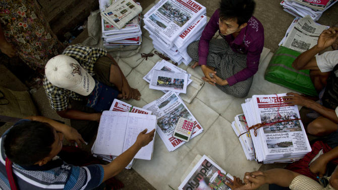 Retailers sort newspapers on a sidewalk in Yangon, Myanmar, Monday, April 1, 2013. For most people in Myanmar, it will be a novelty when privately run daily newspapers hit the streets on Monday. Many weren't even born when the late dictator Ne Win imposed a state monopoly on the daily press in the 1960s.(AP Photo/Gemunu Amarasinghe)