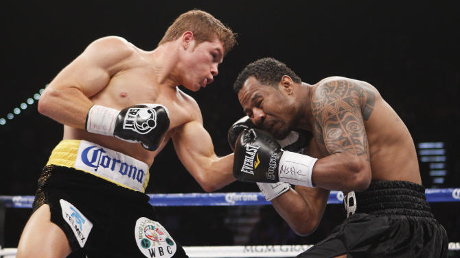 Canelo Alvarez, left, lands a punch against Shane Mosley in the first round during a WBC super welterweight title fight, Saturday, May 5, 2012, in Las Vegas.  (AP Photo/Eric Jamison)
