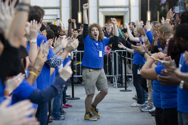 An Apple employee riles up his coworkers outside the Fifth Avenue Apple store to celebrate the release of the iPhone 5, Friday, Sept. 21, 2012, in New York. Hundreds of people waited in line through t