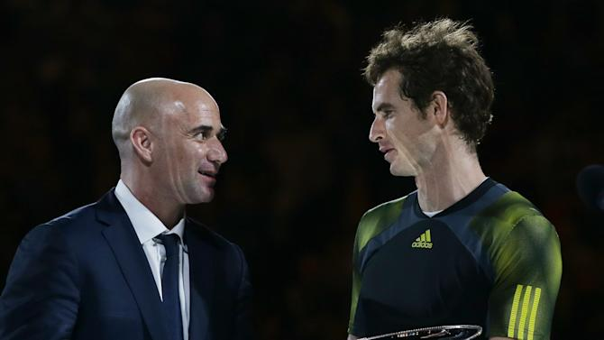Britain's Andy Murray, right, holds the runner up trophy as he chats with former champion Andre Agassi after Murray's loss to Serbia's Novak Djokovic in the men's final at the Australian Open tennis championship in Melbourne, Australia, Sunday, Jan. 27, 2013. (AP Photo/Aaron Favila)