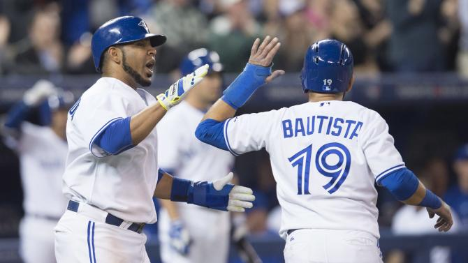 Toronto Blue Jays' Edwin Encarnacion, left, and Jose Bautista celebrate after they scored on a Russell Martin pinch-hit single during eighth inning MLB baseball action against the New York Yankees in Toronto on Monday, May 4, 2015. (Darren Calabrese/The Canadian Press via AP)   MANDATORY CREDIT
