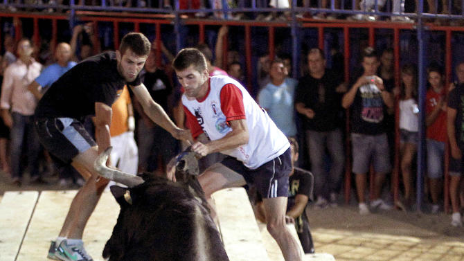 In this Sept. 9, 2011 photo, a reveler runs away from 'Raton' the killer bull in the early hours Sunday, during a festivity in Sueca, near Valencia, Spain, The hulking black and white bull, 'Raton' (Mouse),  a 1,100-pound (500-kilogram) beast who has killed two people in the arena and injured five others over the years at pueblo (village) parties where he's released in a ring and amateur daredevils provoke him so he'll chase them around to the cheers of thousands. Nobody got killed this time. (AP Photo/Alberto Saiz)