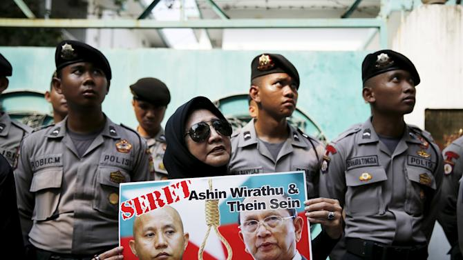 An Indonesian woman holds a poster of Myanmar's President Thein Sein and Buddhist monk Ashin Wirathu during a protest against Wirathu as police stand guard in front of the Myanmar embassy in Jakarta,