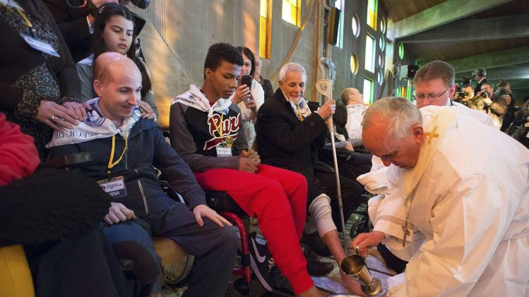 Pope Francis washes the foot of a disabled person at the S. Maria della Provvidenza church in Rome, during Holy Thursday celebration