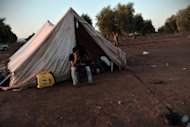A Free Syrian Army fighter sits outside a tent at an unofficial rebel camp set up in an olive grove near the Syrian-Turkish border in August 2012. The source of the winter fuel that some Syrian farmers will use is not crude, but olives