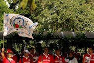 A worker waves a National Union of Bank Employees flag during a May Day rally in Kuala Lumpur. Malaysia will introduce a minimum wage for the first time in a move to bolster incomes amid rising living costs and speculation of a snap general election, a report said
