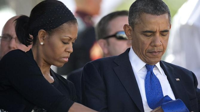 President Barack Obama looks down as first lady Michelle Obama, left, adjusts his tie before the start of a memorial service for the late Sen. Daniel Inouye, D-Hawaii, at the National Memorial Cemetery of the Pacific, Sunday, Dec. 23, 2012, in Honolulu. Inouye, 88  was the first Japanese-American elected to both houses of Congress and the second-longest serving senator in U.S. history. (AP Photo/Carolyn Kaster)