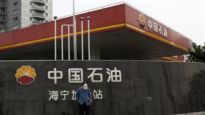 A garbage collector stands in front of a PetroChina company logo at its gas station in Shanghai