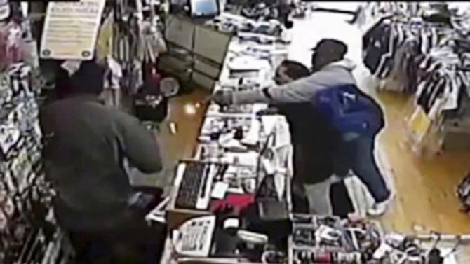 In this image taken from Tuesday, April 9, 2013 surveillance video provided courtesy of Quizhpe Gifts & Fashion, an armed robber, right, holding onto the shop owner Luis Quizhpe's brother-in-law, fires his gun at Quizhpe, obscured by a second robber at left, during a robbery attempt in Chicago's Logan Square neighborhood. The gunman fired multiple shots at Quizhpe, hitting him in the leg. But the wound failed to stop the shop owner's vigorous counterassault with a baseball bat against the pair of robbers. One man was charged with attempted murder and armed robbery and officers are searching for a second suspect in the incident. (AP Photo/Courtesy Quizhpe Gifts & Fashion)