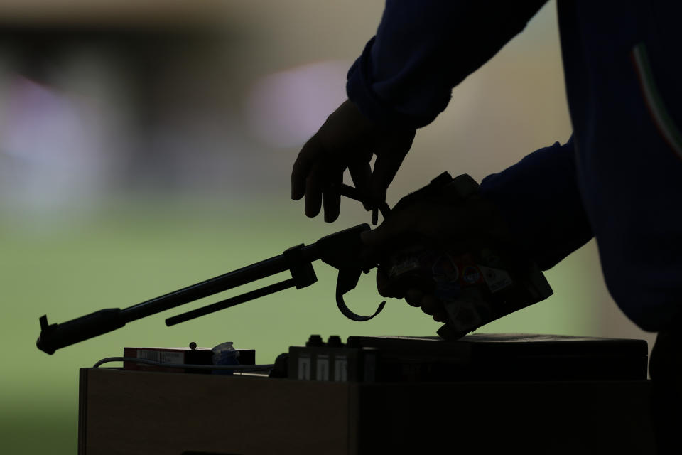 Iran's Ebrahim Barkhordari loads his gun during qualifiers for the men's 50-meter pistol event, at the 2012 Summer Olympics, Sunday, Aug. 5, 2012, in London. (AP Photo/Rebecca Blackwell)