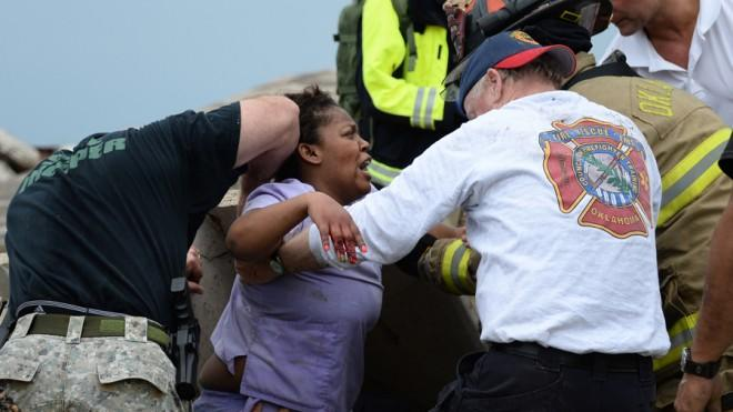 Workers help free a woman trapped at the Moore hospital complex on Monday.