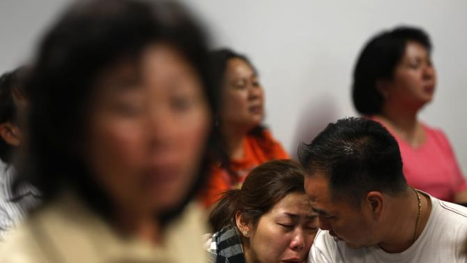 Family of passengers onboard AirAsia flight QZ8501 react at a waiting area in Juanda International Airport, Surabaya