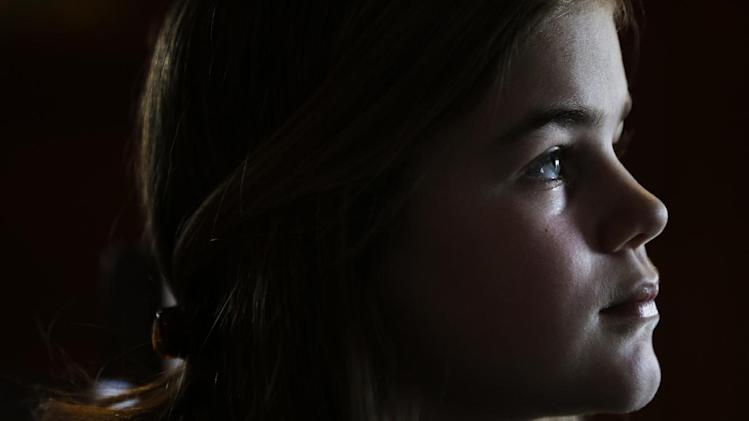 Caroline Pla, 11, listens to a question during an interview Thursday, Feb. 21, 2013, in Doylestown, Pa. Pla is fighting the Roman Catholic Archdiocese of Philadelphia for the right to continue playing church sponsored youth football. (AP Photo/Matt Rourke)