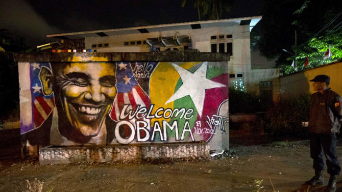 A policeman watches a graffiti done by artist Arker Kyaw welcoming U.S. President Barack Obama in Yangon, Myanmar, at dawn on Saturday, Nov. 17, 2012. When Arker Kyaw heard Obama was coming to Myanmar, he gathered 15 cans of spray paint and headed for a blank brick wall under cover of darkness. Kyaw, whose passion is graffiti, labored from 3 am until the sun came up. (AP Photo/Gemunu Amarasinghe)