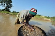 A diamond prospector filters earth from a river in April in Koidu, the capital of the diamond-rich Kono district, in eastern Sierra Leone, some 250 km east from Freetown. Small-scale artisanal mining has sustained this area since diamonds were discovered in 1930, and it was here that the 968.9-carat Star of Sierra Leone was found in 1972 -- the largest alluvial diamond ever found