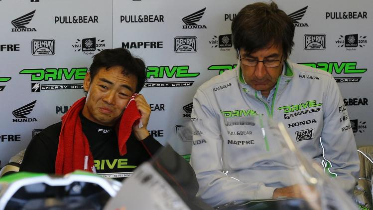 Honda MotoGP rider Hiroshi Aoyama of Japan wipes his face after a warm up session for the British Grand Prix at the Silverstone Race Circuit