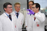 In this file photo, obtained from the London Organising Committee of the Olympic and Paralympic Games, Sports Minister Hugh Robertson (L), London 2012 Chief Executive Paul Deighton (2nd L), and CEO of GlaxoSmithKline Andrew Witty (2nd R), are shown a vial of blood by British professor David Cowan, the head of Science for London 2012 and director of King's College London's Drug Control Centre