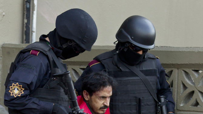 """FILE - In this Jan. 6, 2012 file photo, Baltazar Saucedo Estrada, alias """"El Mataperros,"""" or """"The Dog Killer,"""" is escorted by members of the new Fuerza Civil police force as he is presented to the press in Monterrey, Mexico. According to police, Saucedo is an alleged member of the Zetas drug cartel and ordered his henchmen to set fire to a casino in the northern city of Monterrey in 2010 to punish the owners for failing to pay protection money, which killed 53 people. The source of his nickname remains unclear: Cartels sometimes refer to rivals and police as """"dogs,"""" and cartel recruits reportedly are ordered to hack up the animals as training for human dismemberment. (AP Photo/Hans-Maximo Musielik, File)"""