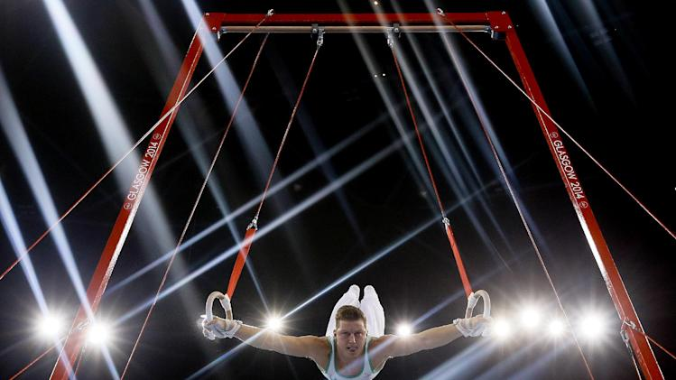 Lights flare as Harry Owen of Wales performs on the rings during the Men's All-Around gymnastics competition at the Scottish Exhibition Conference Centre during the Commonwealth Games 2014 in Glasgow, Scotland, Wednesday July 30, 2014. (AP Photo/Kirsty Wigglesworth)