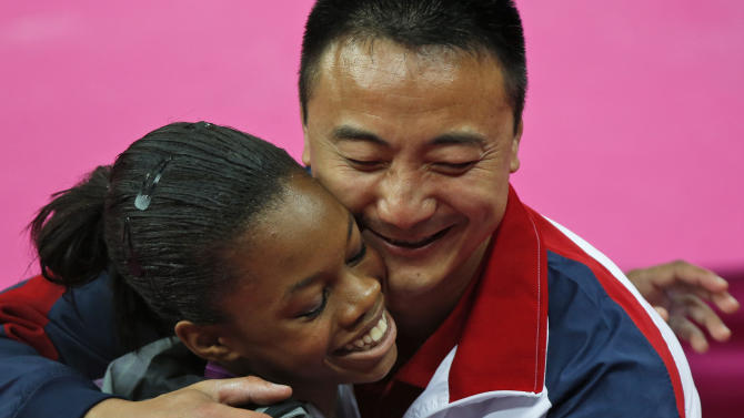 U.S. gymnast and gold medallist Gabrielle Douglas is hugged by coach Liang Chow during the artistic gymnastics women's individual all-around competition at the 2012 Summer Olympics, Thursday, Aug. 2, 2012, in London.  (AP Photo/Matt Dunham)