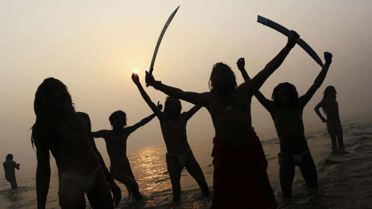 Indian Hindu holy men, or Sadhus, are silhouetted as they celebrate in the water at Sangam, the confluence of the rivers Ganges, Yamuna and mythical Saraswati, during the royal bath on Makar Sankranti at the start of the Maha Kumbh Mela in Allahabad, India, Monday, Jan. 14, 2013. Millions of Hindu pilgrims are expected to take part in the large religious congregation that lasts more than 50 days on the banks of Sangam during the Maha Kumbh Mela in January 2013, which falls every 12th year. (AP Photo/Kevin Frayer)