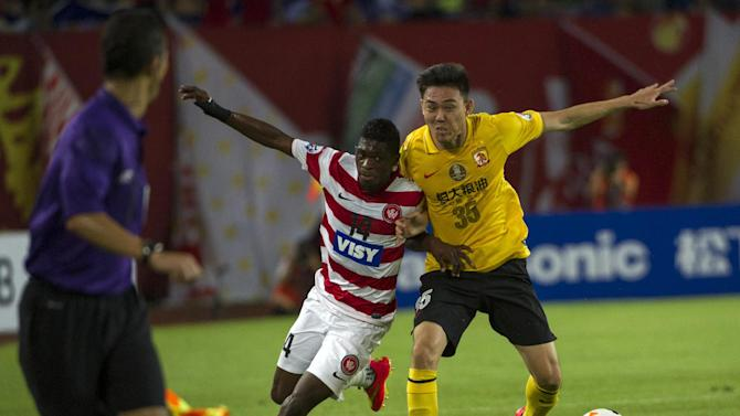 Kwabena Appiah (centre) of Australia's Western Sydney Wanderers tussles for the ball against Li Xuepeng of China's Guangzhou Evergrande during their AFC Champions League quarterfinal match at the Tianhe Sport Center in Guangzhou on August 27, 2014