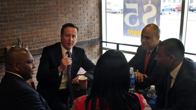 British Prime Minister David Cameron, center left, and Newark Mayor Cory Booker, center right, sit and visit with patrons in a cafe during a short walking tour in Newark, N.J., Thursday, March 15, 2012. Cameron is finishing his official trip to the United States with a visit to the New York City area that includes a meeting at the New York Stock Exchange and a conversation with students at New York University.  (AP Photo/Mel Evans)