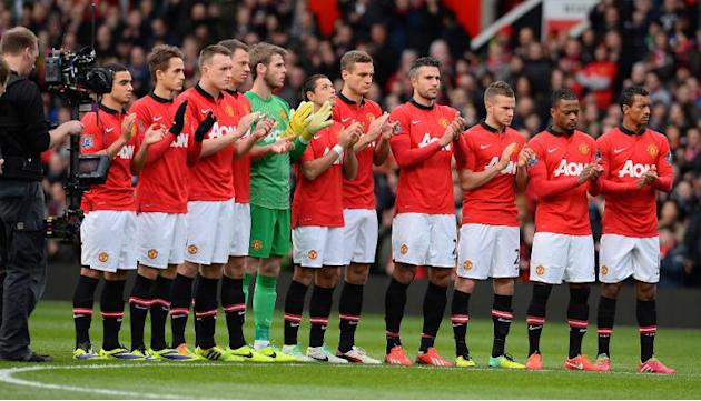 Manchester United players appalud for a minute in tribute to Nelson Mandela before the start of their English Premier League football match against Newcsatle United in Manchester on December 7, 2013