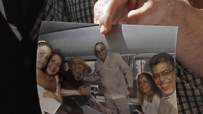 ALTERNATIVE CROP OF XRE101.- Former Venezuelan Vice President Elias Jaua shows a picture of Cuba's leader Fidel Castro,  third from left,  at the Hotel Nacional in Havana Sunday Oct. 21, 2012. According to Jaua, the picture was taken Saturday Oct. 20, 2012  inside a van outside the hotel. A top executive of the hotel told the AP 86-year-old Fidel Castro appeared in public for the first time in months at the hotel Saturday challenging persistent rumors that the aging revolutionary is near death. Others in the picture being held by Jaua are, Antonio Martinez, director of the Hotel Nacional, center, Castro's wife, Dalia Soto del Valle, second from right, and Jaua at right. The two women at left are unidentified.(AP Photo/Franklin Reyes)