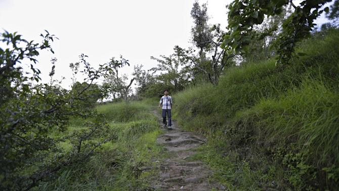 In this Aug. 24, 2012 photo, Bhuwan Butholia, like many of his colleagues, walks through the hilly terrain on his way to and from the B2R center in Simayal, India. Before B2R arrived in Simayal, Butholia used to work in an auto parts factory 150 kilometers (90 miles) away, spending whatever he earned on food and rent. (AP Photo/Saurabh Das)