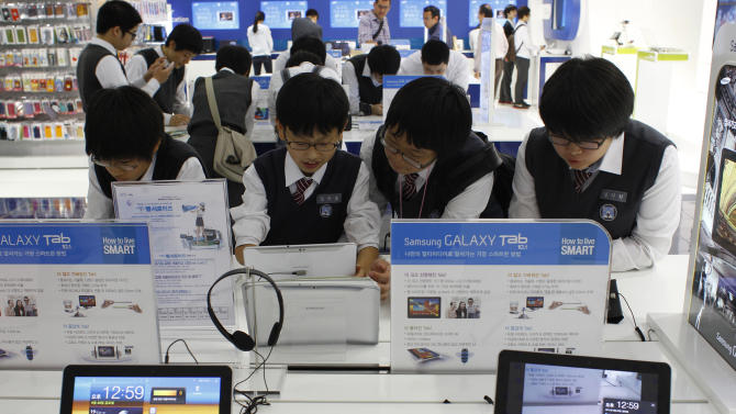 South Korean students use Samsung Electronics' new tablet Galaxy Tab 10.1 at its showroom in Seoul, South Korea, Friday, Sept. 23, 2011. A top Samsung Electronics Co. executive says her company will take a more aggressive stance against its smartphone and tablet rival Apple Inc. in a global patent dispute. (AP Photo/Lee Jin-man)