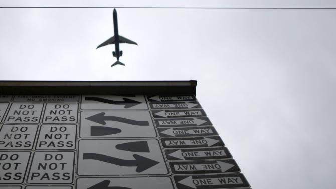 A plane flies past a mural made from more than 500 highway signs in Phoenix