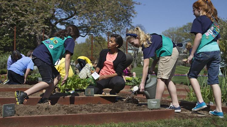 FILE - In this March 26, 2012, file photo, first lady Michelle Obama, center, talks to Girl Scouts, from left, Gia Muto, Emma Vonderlinn and Emily Burnham, all from Fairport, N.Y. as they plant potatoes in the White House garden in Washington. From the beginning, Obama's kitchen garden has been an overachiever, churning out more peppers, parsley and eggplant than expected, and generating interest that _ yes, really _ crosses oceans. (AP Photo/Manuel Balce Ceneta)