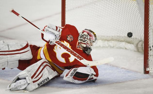 Calgary Flames goalie Joni Ortio, from Finland, looks back at a goal by the New York Islanders during the second period of an NHL hockey game Friday, March 7, 2014, in Calgary, Alberta