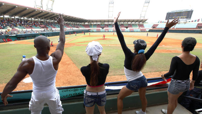 In this picture taken Sunday April 22, 2012, young men and women dance in the front row during the Cuban National Baseball Series between the Holguin home team and the Havana-based Metropolitanos, a farm team of the better-known Industriales at the local stadium in Holguin, Cuba.  (AP Photo/Kathy Willens)