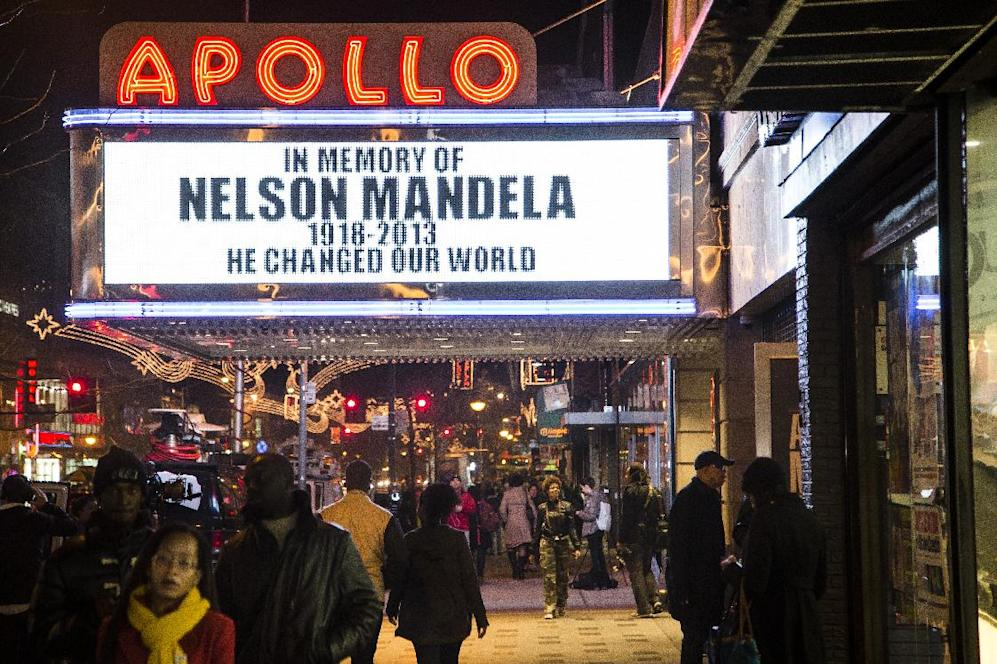 Pedestrians pass beneath the Apollo Theatre marquee commemorating the life of South African leader Nelson Mandela, Thursday, Dec. 5, 2013, in the Harlem neighborhood of New York. South Africa's first black president died Thursday after a long illness. He was 95. (AP Photo/John Minchillo)