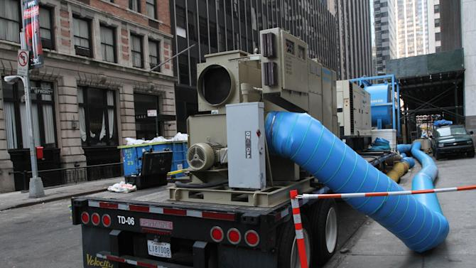 In this Friday, Nov. 23, 2012 photo, a dehumidifier, parked on Front Street near Wall Street in New York, blows dry air into the basement of a nearby building. Parts of lower Manhattan's Financial District are still laboring to recover nearly a month after Superstorm Sandy. A real estate consulting firm says that of the nearly 50 office buildings shut down after Sandy buffeted the Financial District, about half have reopened. Some of the others that are home to large financial and law firms still could be closed for weeks, if not months. (AP Photo/Tina Fineberg)