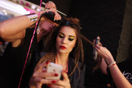 A model has her hair done backstage before the Betsey Johnson Spring 2013 collection show during Fashion Week, Tuesday, Sept. 11, 2012, in New York. (AP Photo/Jason DeCrow)
