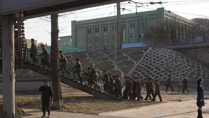 """FILE - In this Friday, April 12, 2013 file photo, North Korean soldiers climb stairs on a street overpass in Pyongyang, North Korea. Enemy capitals, North Korea said, will be turned """"into a sea of fire."""" North Korea's first strikes will be """"a signal flare marking the start of a holy war.""""  Pyongyang's nuclear arsenal is """"mounted on launch pads, aimed at the windpipe of our enemies."""" And it's not all talk. The profoundly isolated, totalitarian nation has launched two rockets over the past year. But there is also a logic behind North Korea's behavior, a logic steeped in internal politics, one family's fear of losing control and the ways that a weak, poverty-wracked nation can extract concessions from some of the world's most fearsome military powers. (AP Photo/David Guttenfelder, File)"""