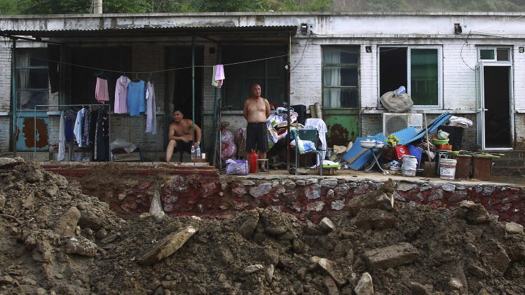 In this photo taken on Monday, July 23, 2012, Chinese villager look at courtyard damaged by flood at their home in Fangshan district in Beijing. Recent heavy rains across much of China have left nearly 100 people dead, state media said Tuesday. More than a third of the fatalities were in the flood-ravaged capital, where some residents questioned whether the city's rapid push for modernization came at the expense of basic infrastructure such as drainage networks. (AP Photo) CHINA OUT