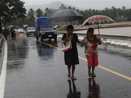 Women use umbrellas while crossing a temporary bridge during rain brought on by Hurricane Raymond in Coyuca de Benitez