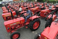 <p>Indian workers inspect new tractors for sale at a Mahindra dealership for agricultural vehicles in Sanand town on August 27, 2012. The central Reserve Bank of India has warned the country's economic prospects are unlikely to improve in the near-term, due to high inflation, the lack of reform and the impact of poor monsoon rains on farm output.</p>