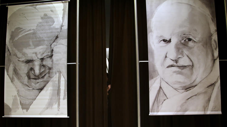 A press hall attendant holds the curtains adorned with portraits of late Pope John Paul II, left, and John XXIII prior to the start of a press conference at the Vatican, Friday, April 25, 2014. Hundred thousands of pilgrims and faithful are expected to reach Rome to attend the scheduled April 27 ceremony at the Vatican in which Pope Francis will elevate in a solemn ceremony John XXIII and John Paul II to sainthood. (AP Photo/Gregorio Borgia)
