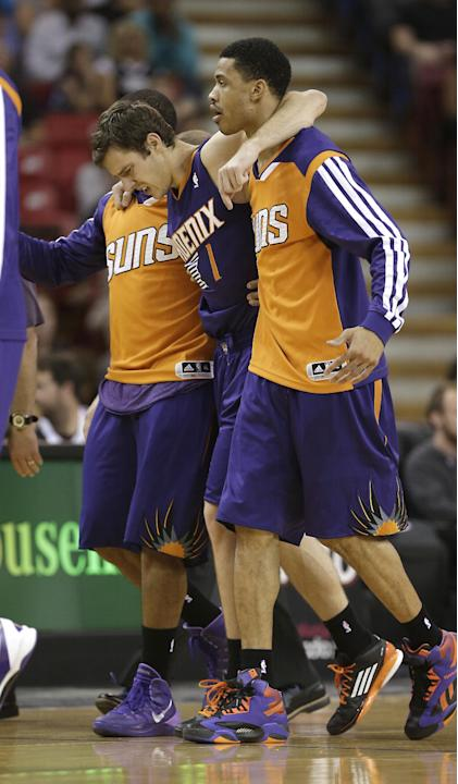 Phoenix Suns guard Goran Dragic, of Slovenia, center, is helped off the court after injuring his ankle during the third quarter of an NBA preseason basketball game in Sacramento, Calif., Thursday, Oct