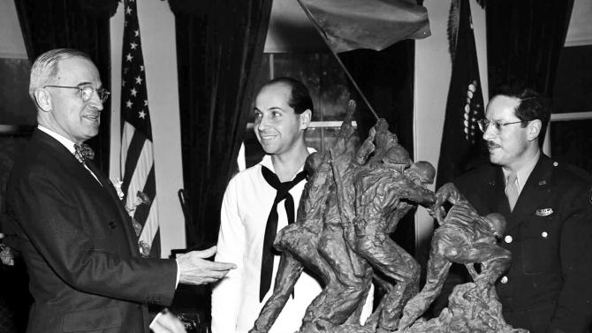 FILE - In this June 4, 1945 file photo, President Harry Truman, left, is presented with a bronze statue by sculptor Felix de Weldon, center, and Associated Press photographer Joe Rosenthal at the White House in Washington. The sculpture, depicting five Marines and a Navy Corpsman raising the flag on the island of Iwo Jima, was inspired by a photo taken by Rosenthal, Feb. 23, 1945. The original 12 1/2-foot-tall statue created by de Weldon soon after Rosenthal took his picture in 1945 is being auctioned Feb. 22, 2013, in New York. (AP Photo/File)